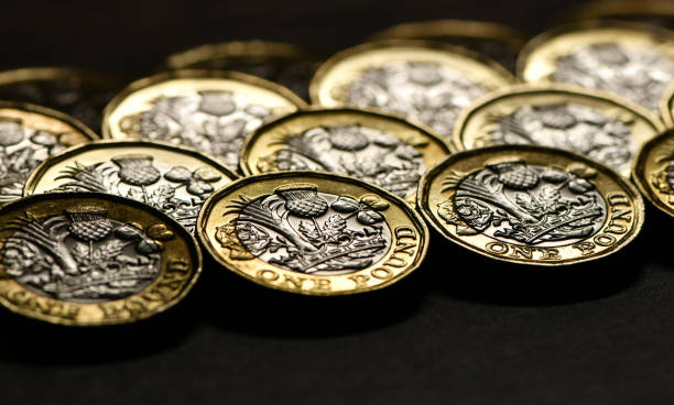 Money being counted - pound coins in a pattern. Business and finance Money being counted on a table made up of silver and gold pound coins. Lined up in a line, stacked and in a heart shape one pound coin stock pictures, royalty-free photos & images