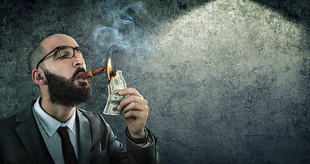 money burning - businessman arrogant - guy with cigar stockfoto's en -beelden