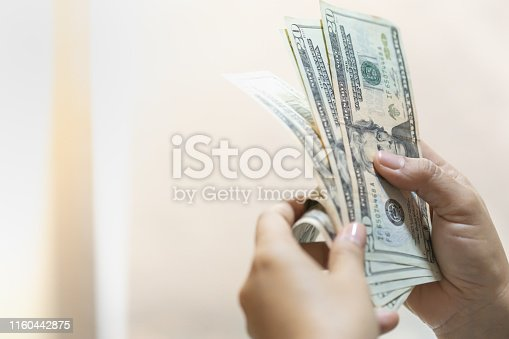 Money Business shopping and saving concept. Close up of woman hand holding and counting US Dollar banknote with copy space.