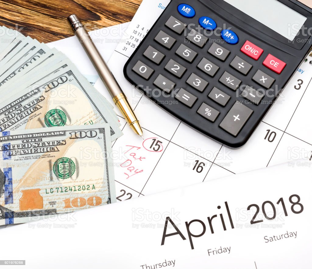 Money, calculator and calendar on the table. Tax time concept. stock photo
