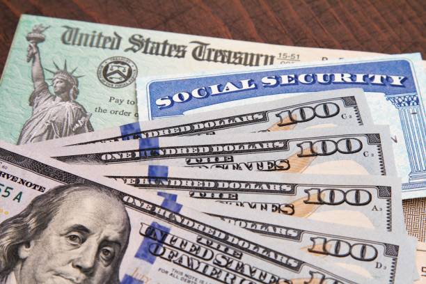 Money: closeup of USA currency with government treasury check and social security card Government spending and benefits concept social security stock pictures, royalty-free photos & images