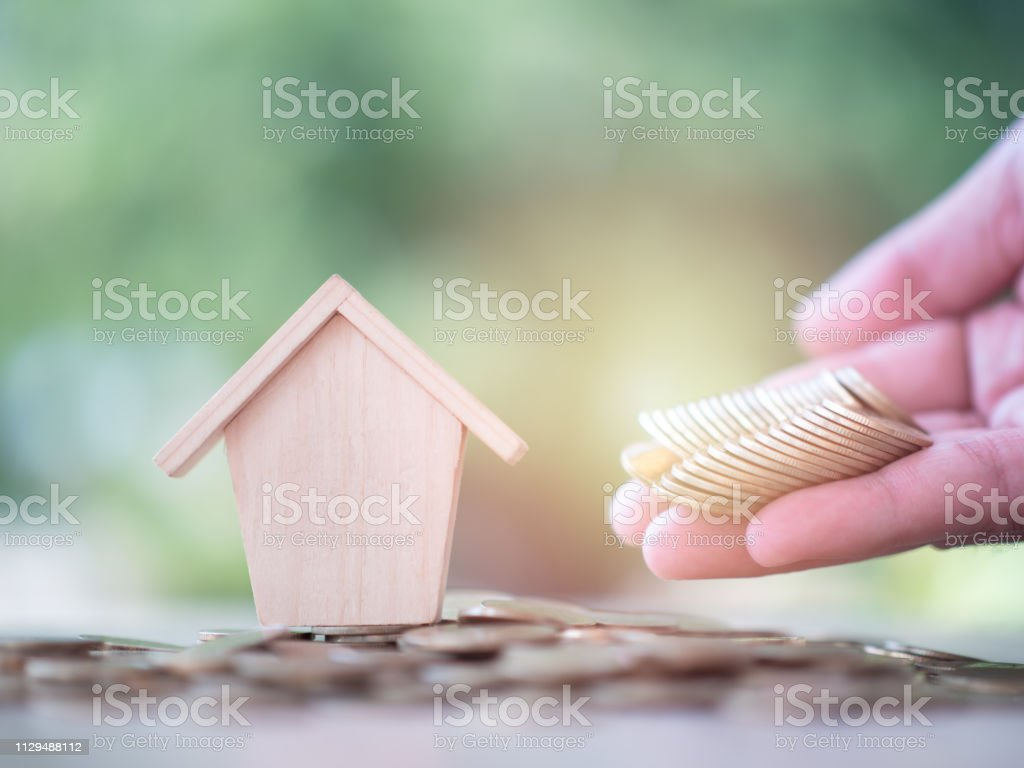 Money coin on hand with home model on nature green background....