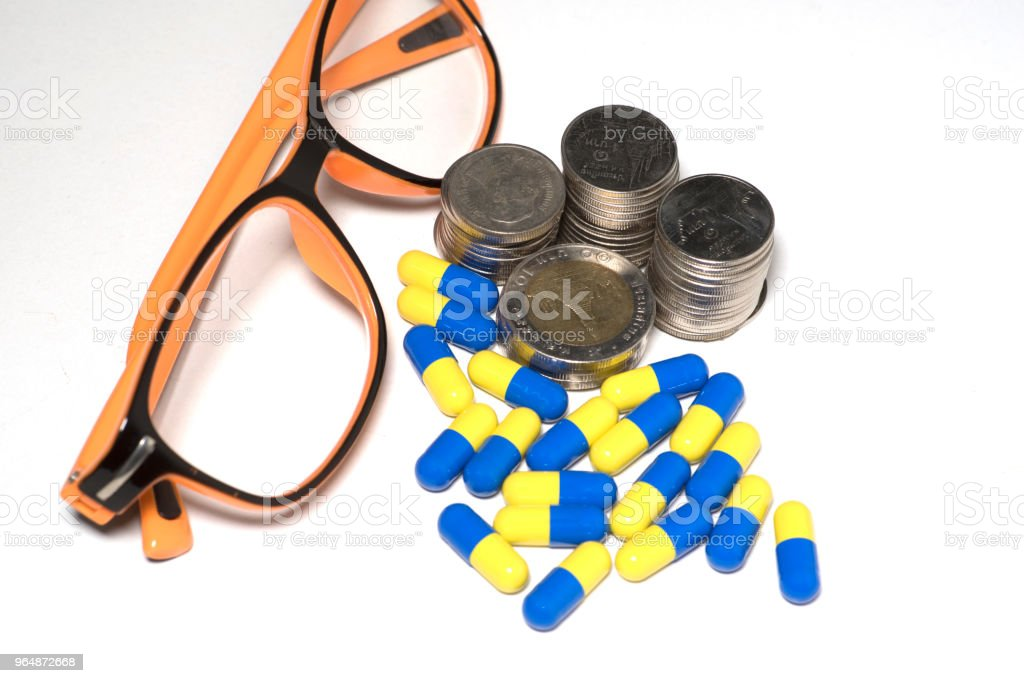 Money coins and tablet drugs as an element of health royalty-free stock photo