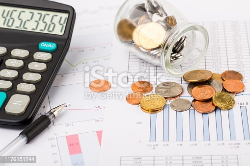 467271788 istock photo Money coins with graph paper and calculator 1176151244