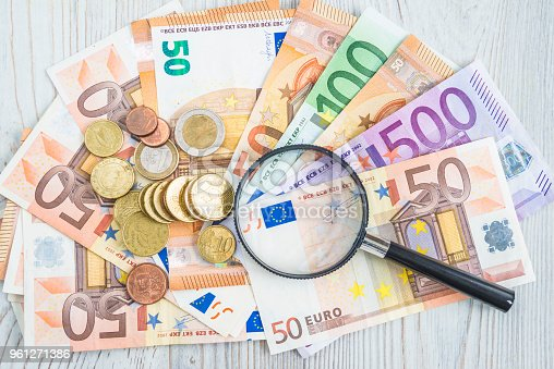Hand lens on euro banknotes and coins