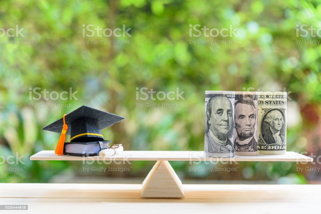 Money cost saving for goal and success in school, education concept : US USD dollar notes or cash, graduation cap, a text book, a certificate / diploma on basic wooden balance scale. Green background. stock photo