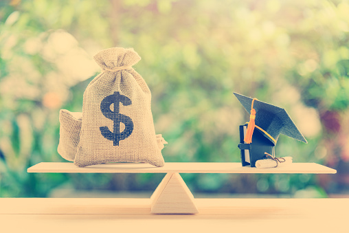Money Cost Saving For Goal And Success In School Education Concept Us Dollar Bills Cash In Hessian Bags A Black Graduation Cap Or Hat A Certificate Diploma And A Book On Simple Balance Scale Stock Photo - Download Image Now