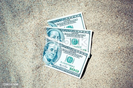 Money dolars half covered with sand lie on beach close-up. Dollar bills partially buried in sand. Three hundred dollars buried in sand on sea ocean beach Concept finance money holiday relax vacation