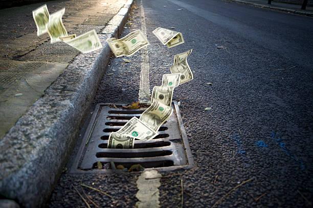 Dinheiro caindo em um poço de inspeção - foto de acervo