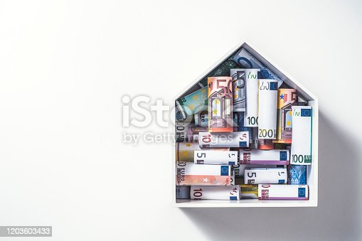 Euro rolls in house shape box, mortgage concept. Money for a house.