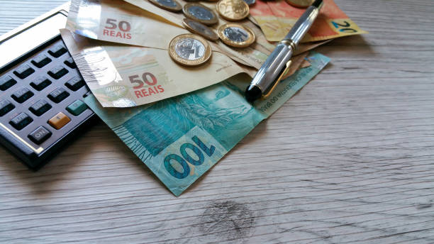 Money from Brazil. Notes of Real, Brazilian currency. Calculator.Concept of economy Money from Brazil. Notes of Real, Brazilian currency. Calculator.Concept of economy wages stock pictures, royalty-free photos & images