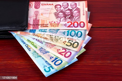 Money from Ghana in the black wallet on a wooden background