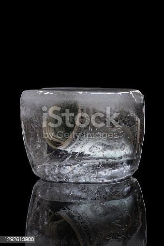 Money froze in the ice. The concept of freezing money deposits. Foreign bank account. Isolated on a black background.
