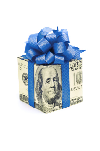 Subject: Horizontal view of a human hand holding a square gift box wrapped with paper of a U.S. one hundred dollar bill, tied with blue ribbon and a fancy bow. The bow color suggests a Hanukkah gift, bonus, birthday present, or special occasion. Isolated on a white background.