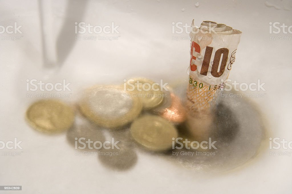 Money going down the drain stock photo