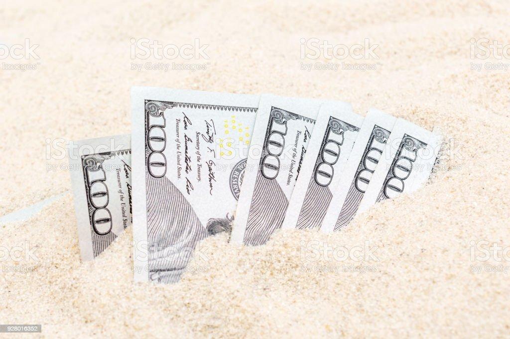Money hidden in the sand. stock photo