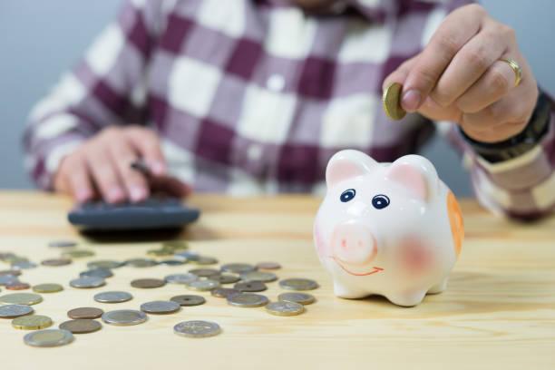 Geld, Haus, Finanzen und Beziehungen Konzept-Mann mit Schwein Bank sitzen am Schreibtisch, Geschäftsmann, Münze in die Sparschweine, Vintage Farbe Morgenlicht – Foto