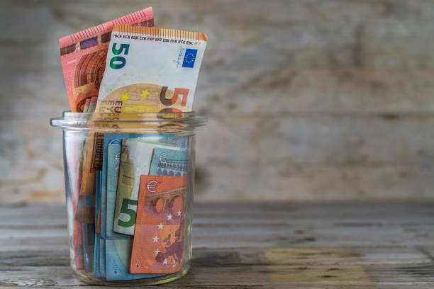 geld im glas. - euro symbol stock-fotos und bilder