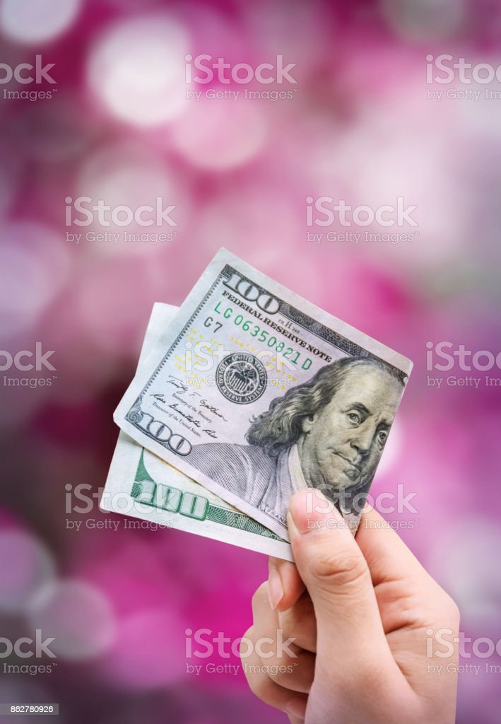 Money in hand, isolated on pink background bokeh stock photo
