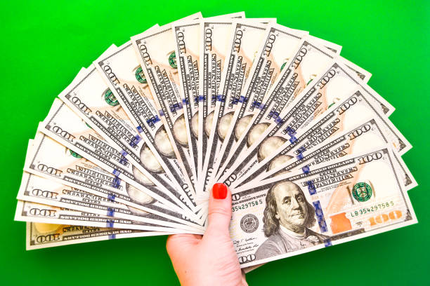 money in hand on green, Top view of female hands counting money stock photo