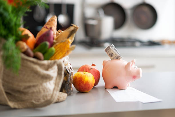 Money in piggy bank and purchases on table. Closeup stock photo