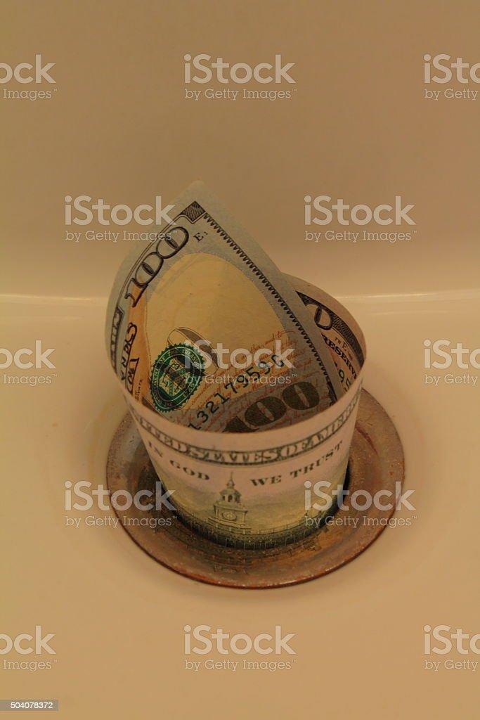 Money in the drain stock photo