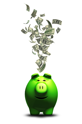 Lots of money falling into smiling  piggy bank. Isolated on white background.