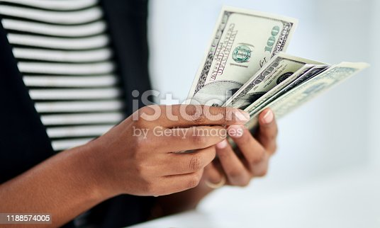 Cropped shot of an unrecognizable businesswoman counting money inside her office at work