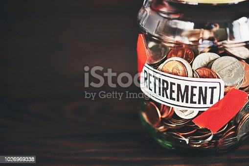 Money jar filled with American coins for retirement