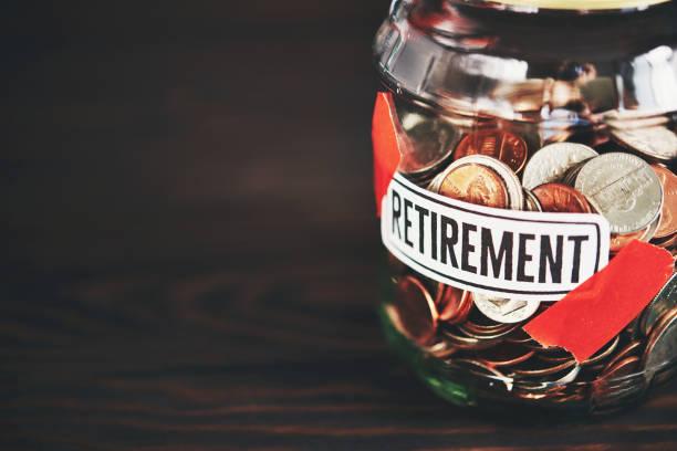 geld-glas, gefüllt mit amerikanischen münzen für den ruhestand - einfache holzprojekte stock-fotos und bilder
