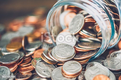 Money jar filled with American currency. Savings and donations concept.