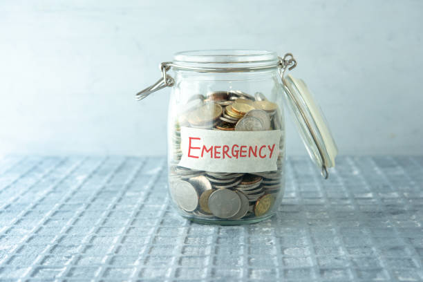 Money jar Coins in glass money jar with emergency label, financial concept. accidents and disasters stock pictures, royalty-free photos & images