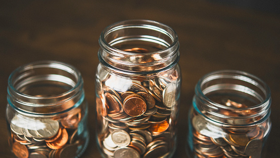 Money jars filled with American currency. Savings and donations concept.