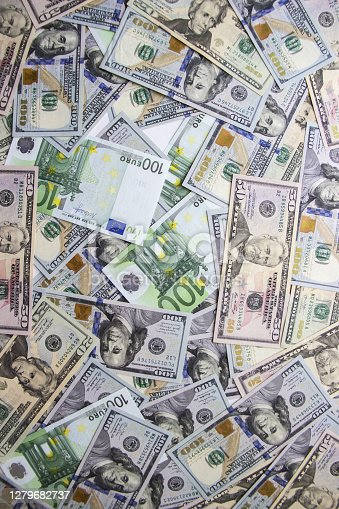 Money lies in a heap on the table scattered. Dollars and euro money lie on the table scattered chaotically.