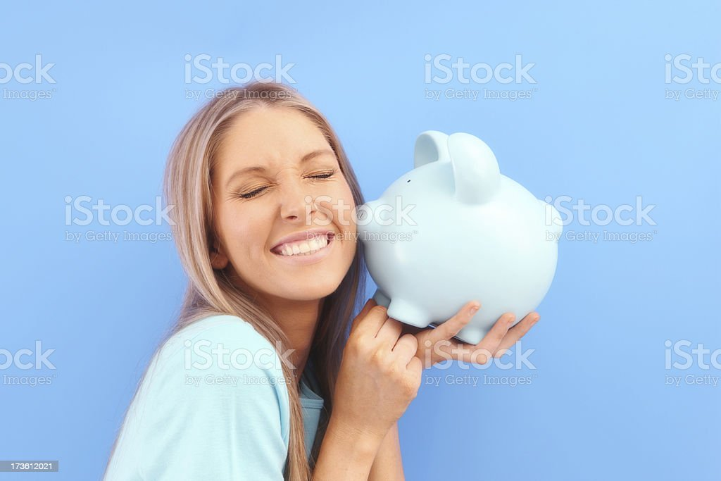 Money Loves Me Woman on blue with piggybank kissing her on the cheek 20-24 Years Stock Photo