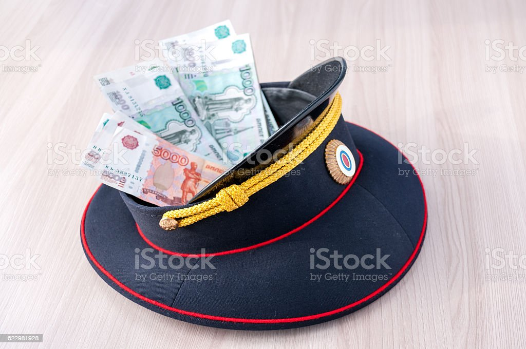 Money lying in a police cap on the table stock photo