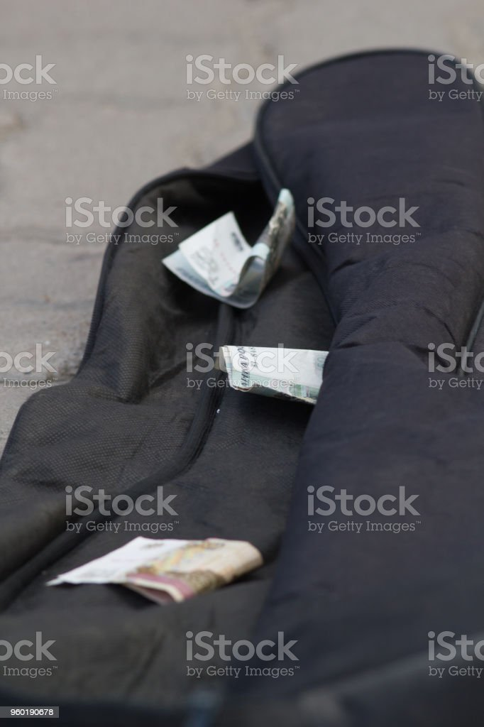 Money of buskers in the guitar case stock photo
