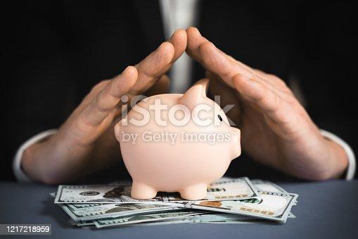 istock Money Protecting concept. Saving symbol - Close-up Of A Human Hand Protecting Pink Piggy Bank 1217218959