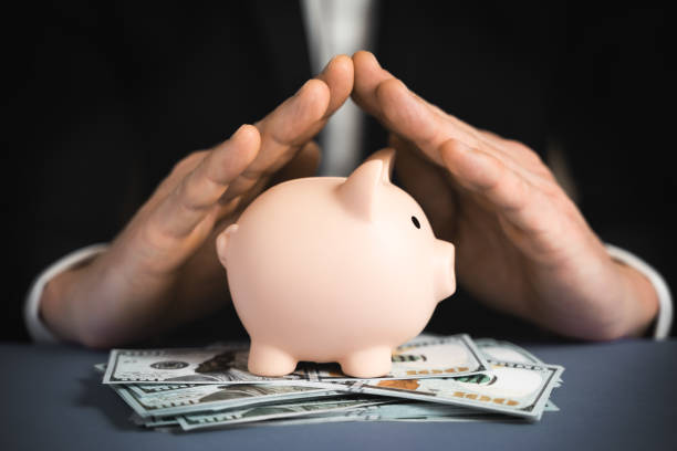 Money Protecting concept. Saving symbol - Close-up Of A Human Hand Protecting Pink Piggy Bank Money Protecting concept. Saving symbol - Close-up Of A Human Hand Protecting Pink Piggy Bank wealth stock pictures, royalty-free photos & images