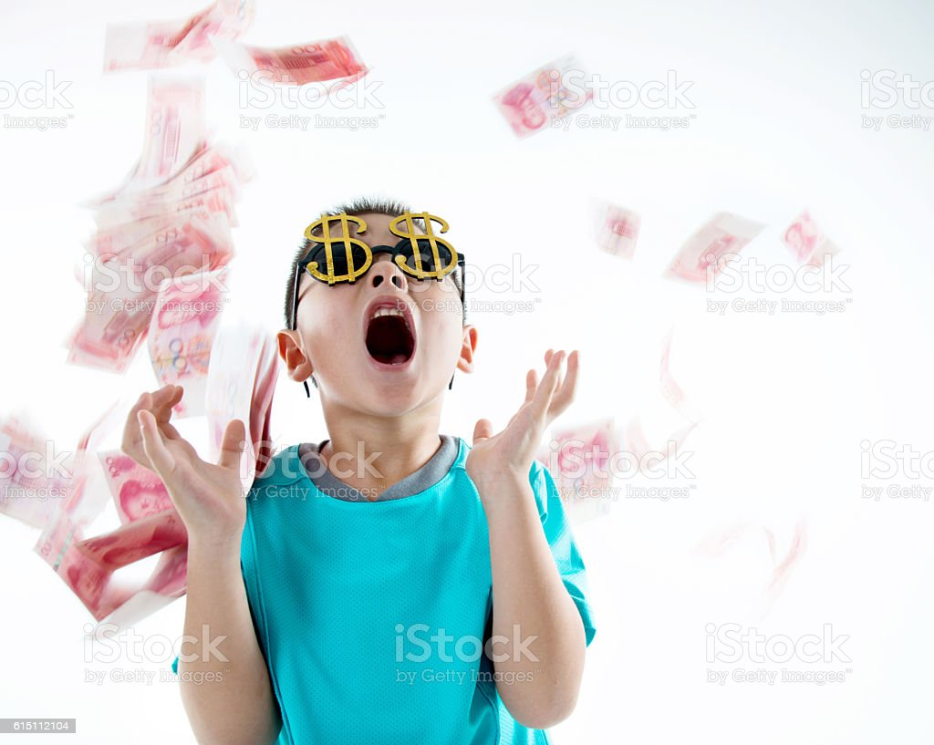 Money rain down onto a laughing boy stock photo