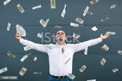 Happy young businessman  throwing 100 dollar banknotes