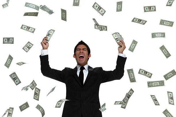 geld regnet auf ein business-mann feiert - sterntaler stock-fotos und bilder