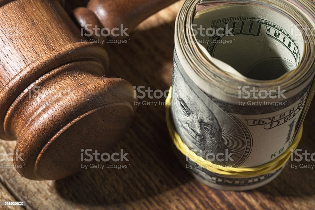 Money roll and judges hammer on wooden table stock photo