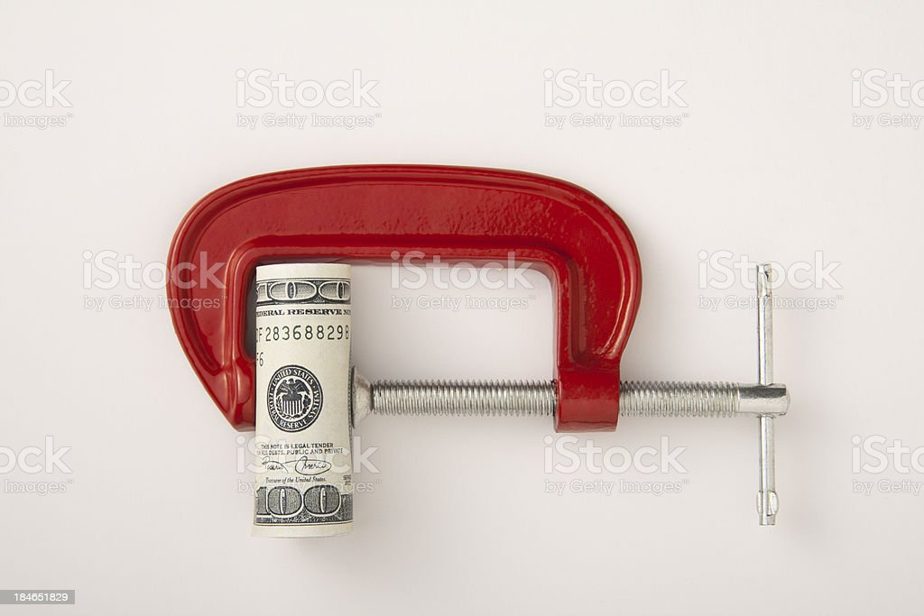 Money roll clamped in a red clamp on a white background stock photo