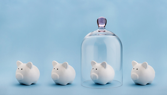 Piggybank protected under a glass dome on blue background