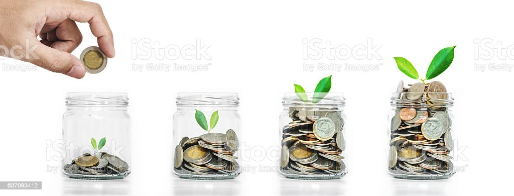 Money saving growth concepts, hand putting coins in glass jar stock photo