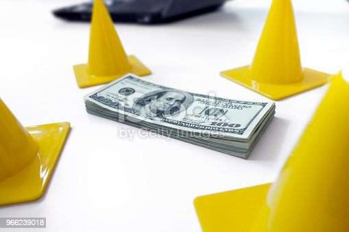 Dollar bills surrounded by traffic cones symboling protecting investments