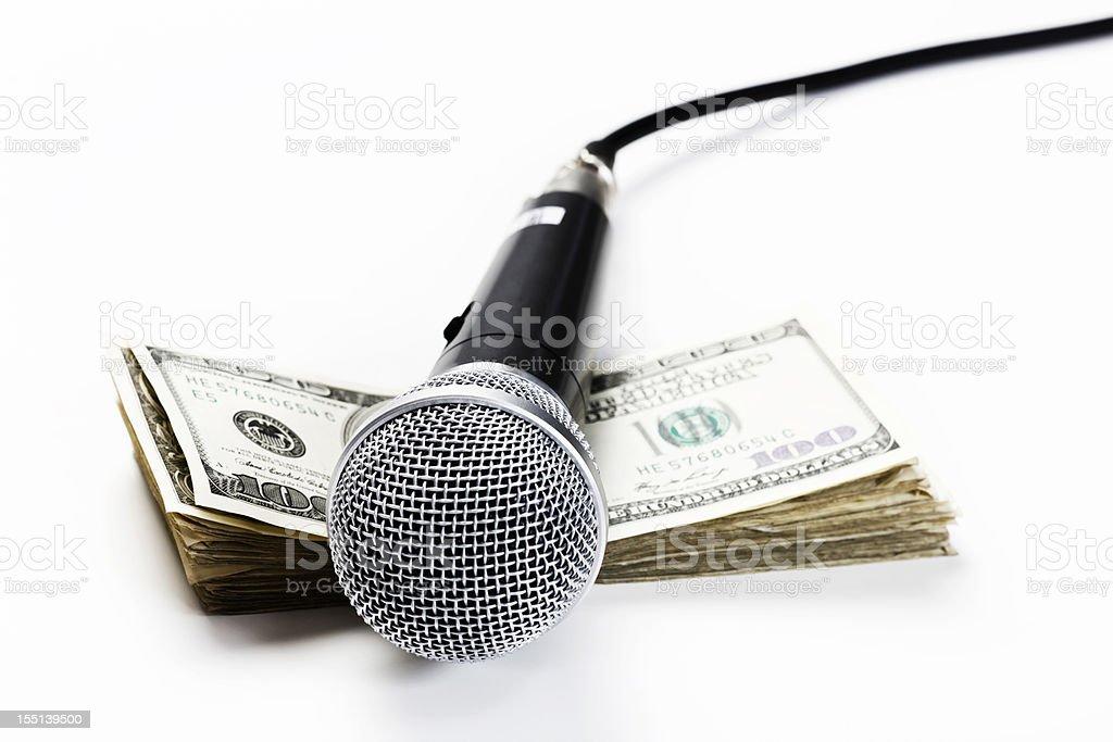 Money talks: microphone on bundle of US dollars stock photo