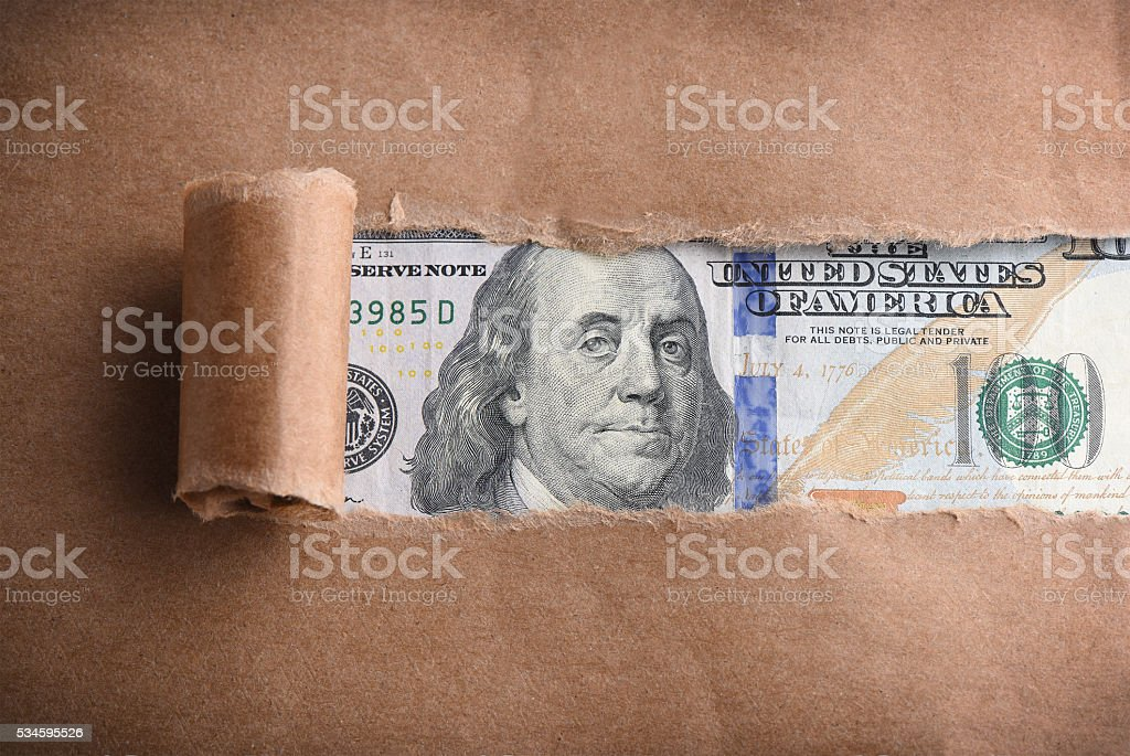 Money  through torn paper stock photo