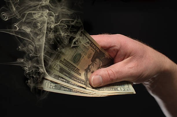 Money To Burn A hand holds money that is burning away. money to burn stock pictures, royalty-free photos & images